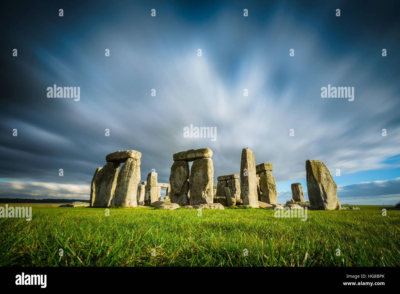 Stonehenge on a sunny and windy winter day. Ancient ruins in Wiltshire, England, no people or tourists. Green grass Stock Photo