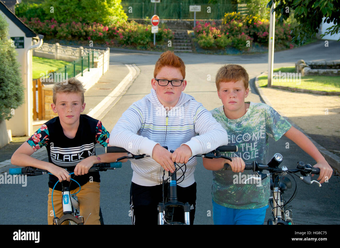 Gang of young boys on bicycles on a suburban street - Stock Image