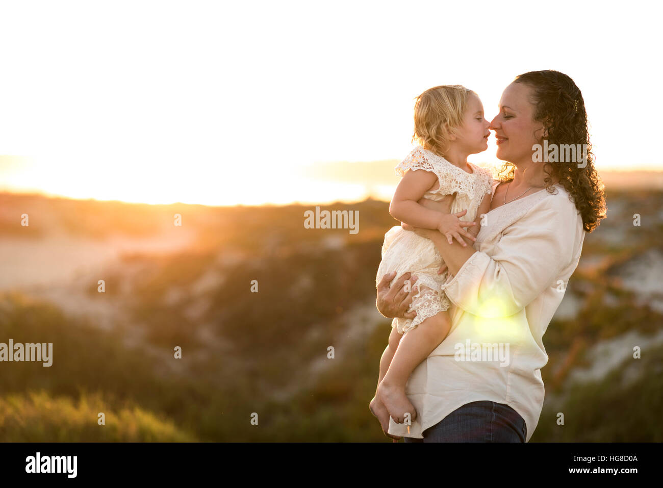 Mother and daughter rubbing noses while standing against clear sky - Stock Image