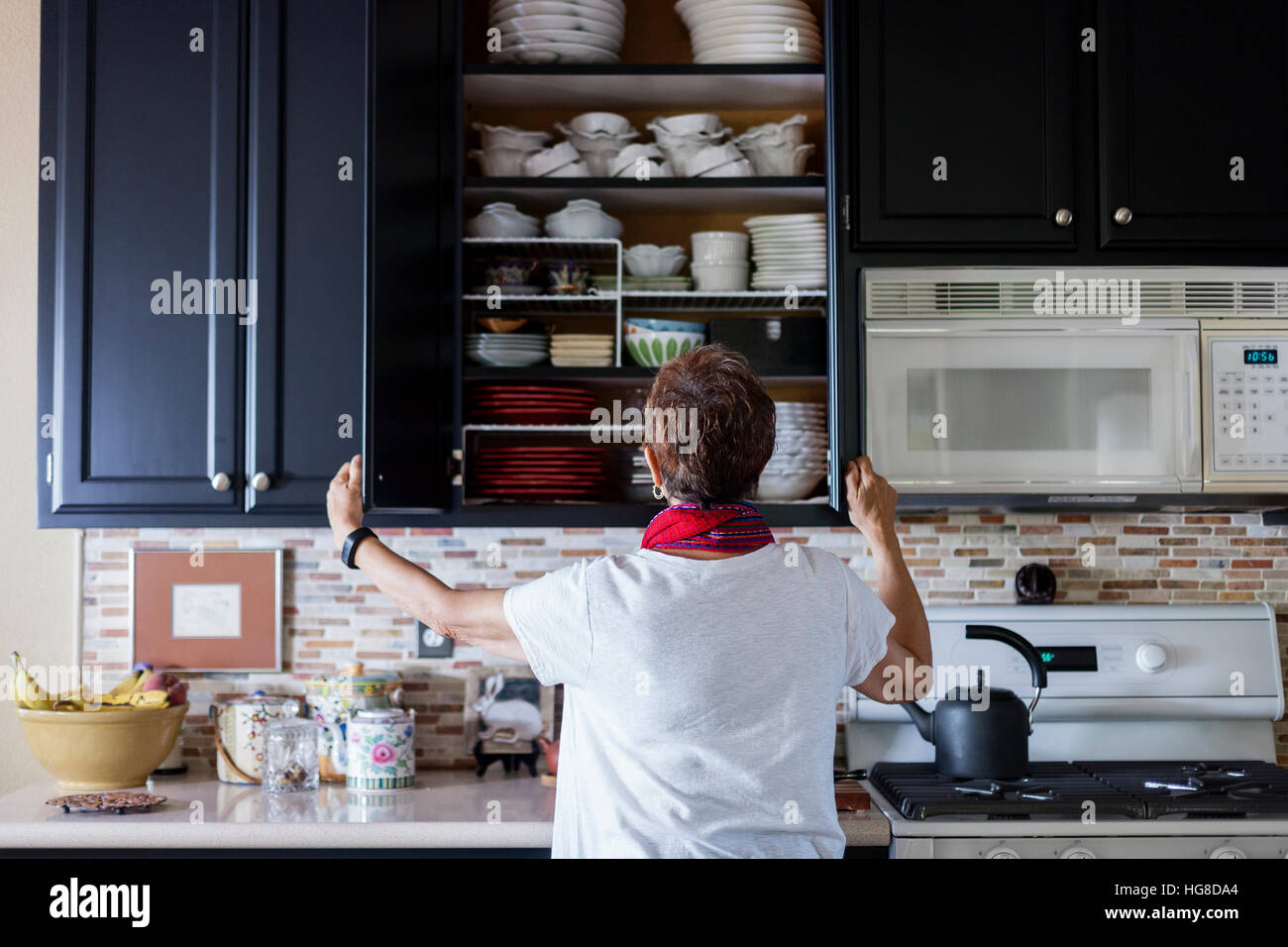Rear view of woman checking cabinet in kitchen Stock Photo