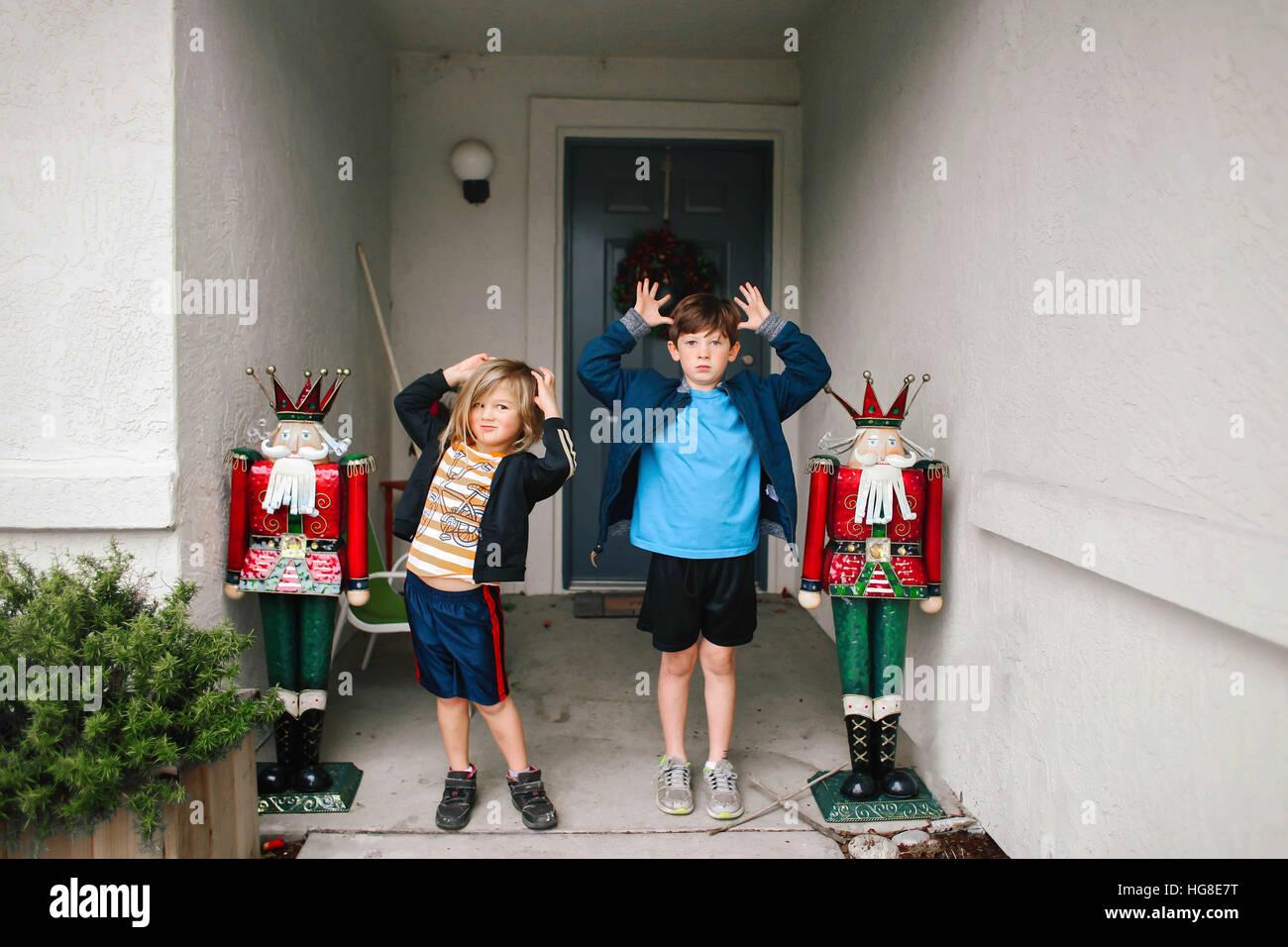 Siblings teasing while standing against door - Stock Image