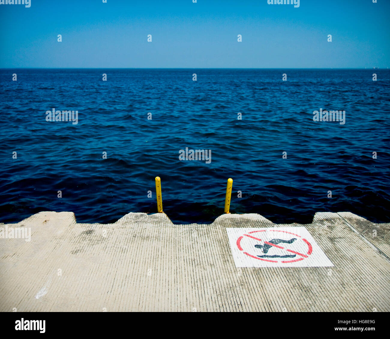 No swimming sign on pier over sea against clear blue sky Stock Photo