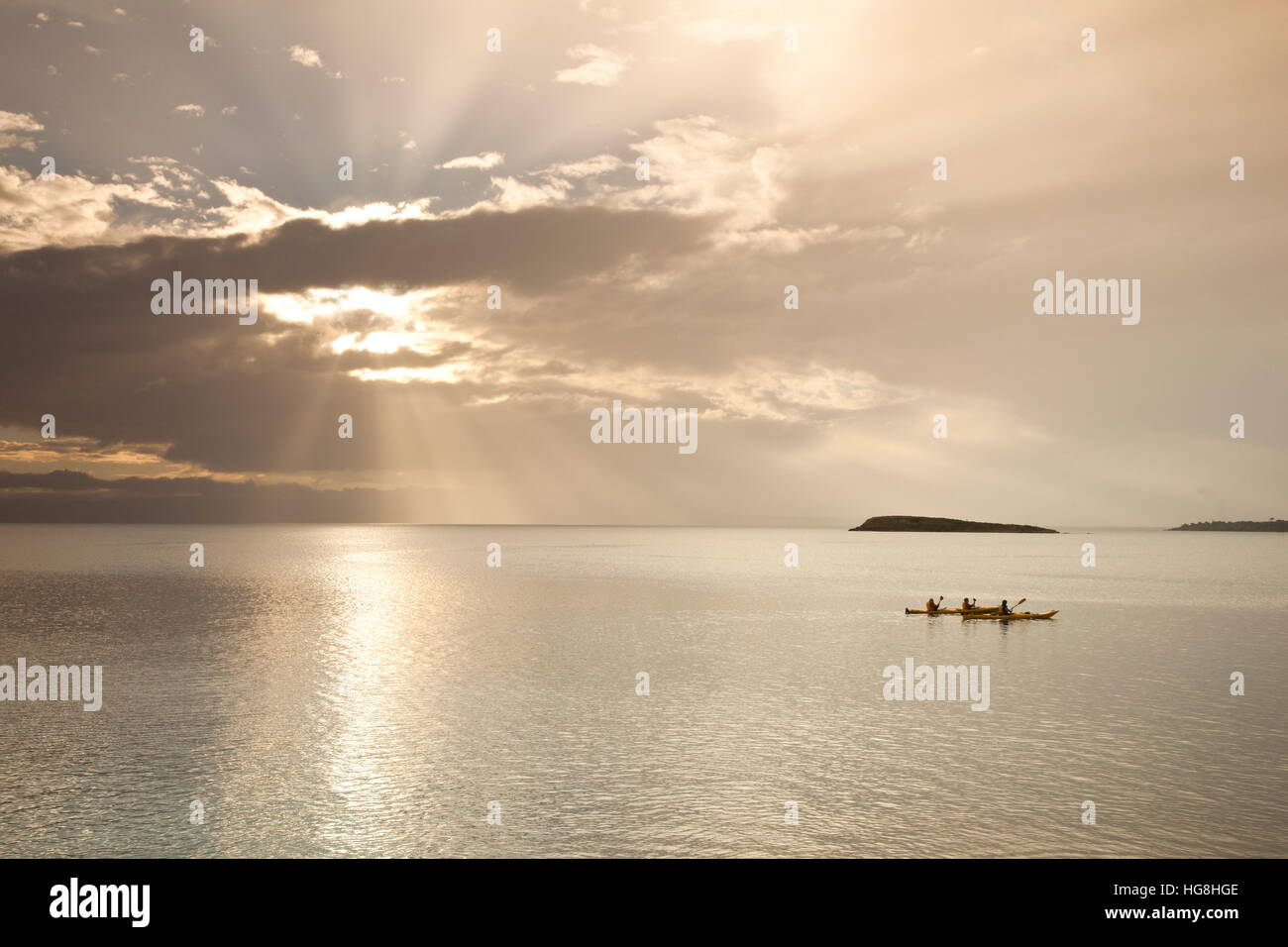 THREE kayakers on calm seas kayaking with sun behind clouds with god's rays of sunlight in Wineglass Bay, Tasmania - Stock Image