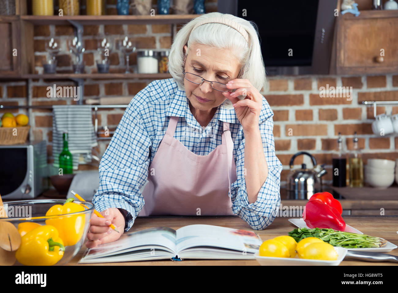 Serious senior woman looking in cookbook while sitting in kitchen Stock Photo