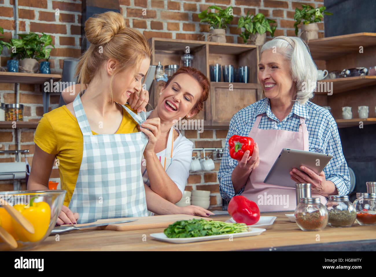 Smiling family cooking together in kitchen - Stock Image