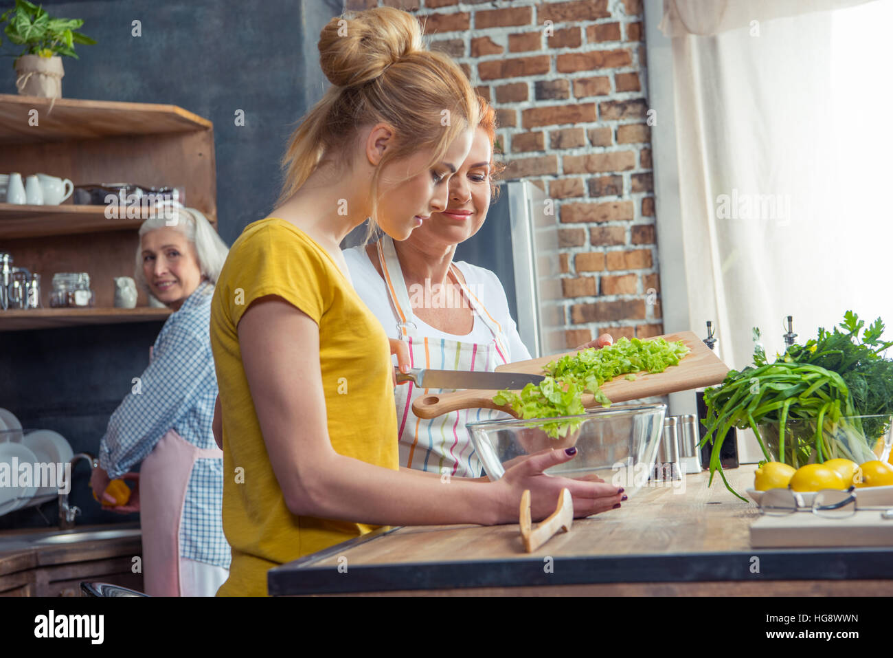 Happy family cooking together vegetable salad in kitchen - Stock Image
