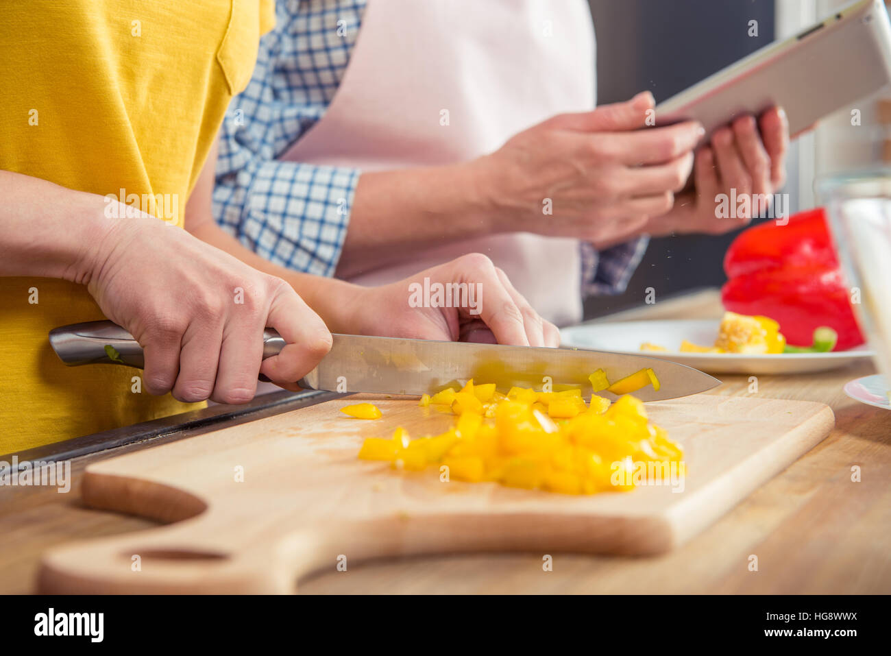Close-up partial view of woman cutting pepper on cutting board - Stock Image