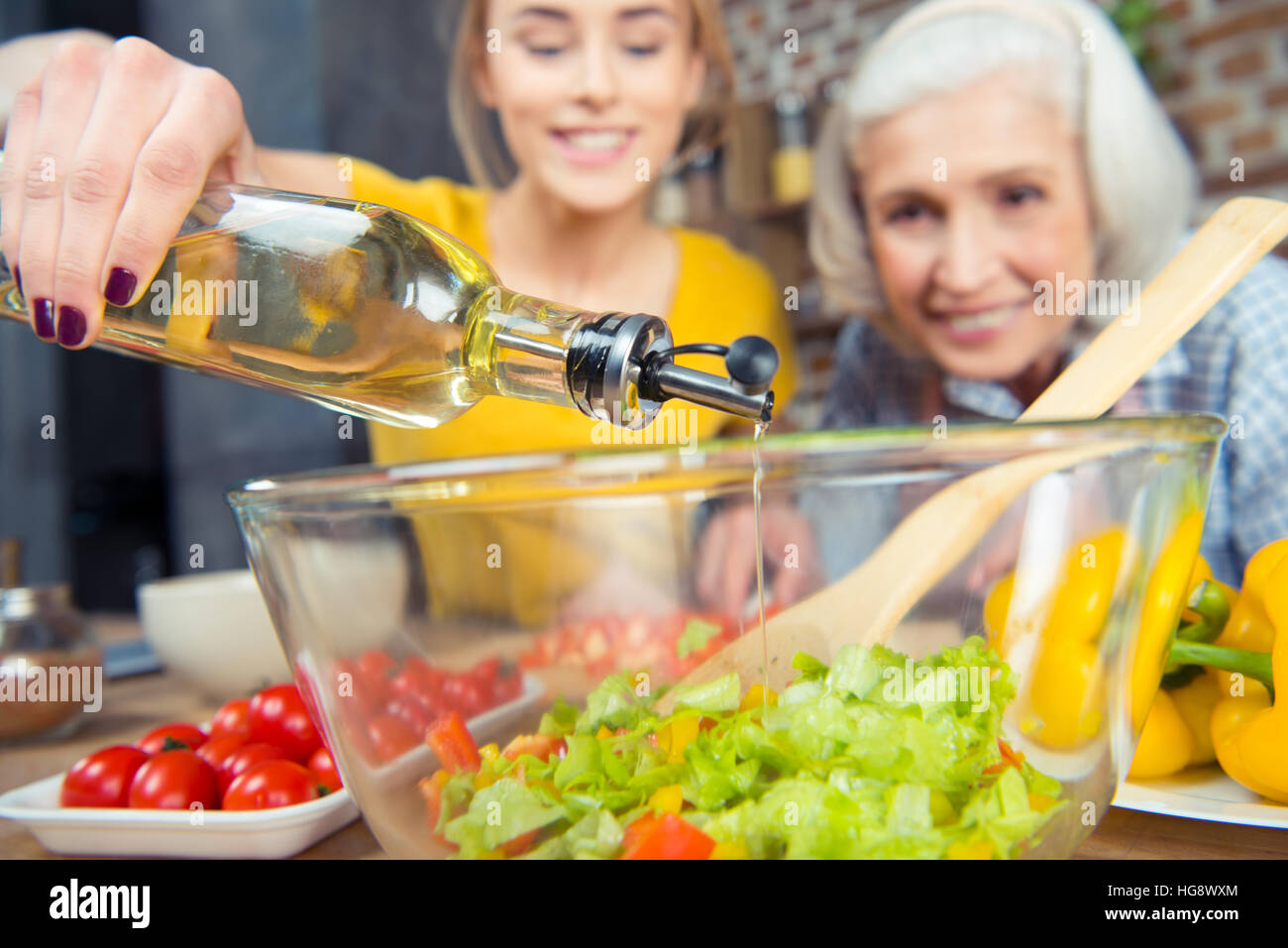 Granddaughter and grandmother cooking together and pouring oil into vegetable salad - Stock Image