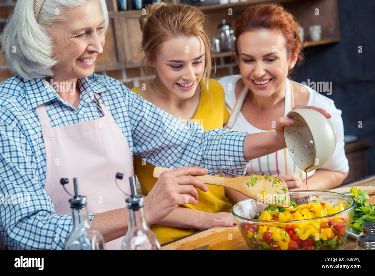 Happy three-generation family cooking vegetable salad together in kitchen Stock Photo