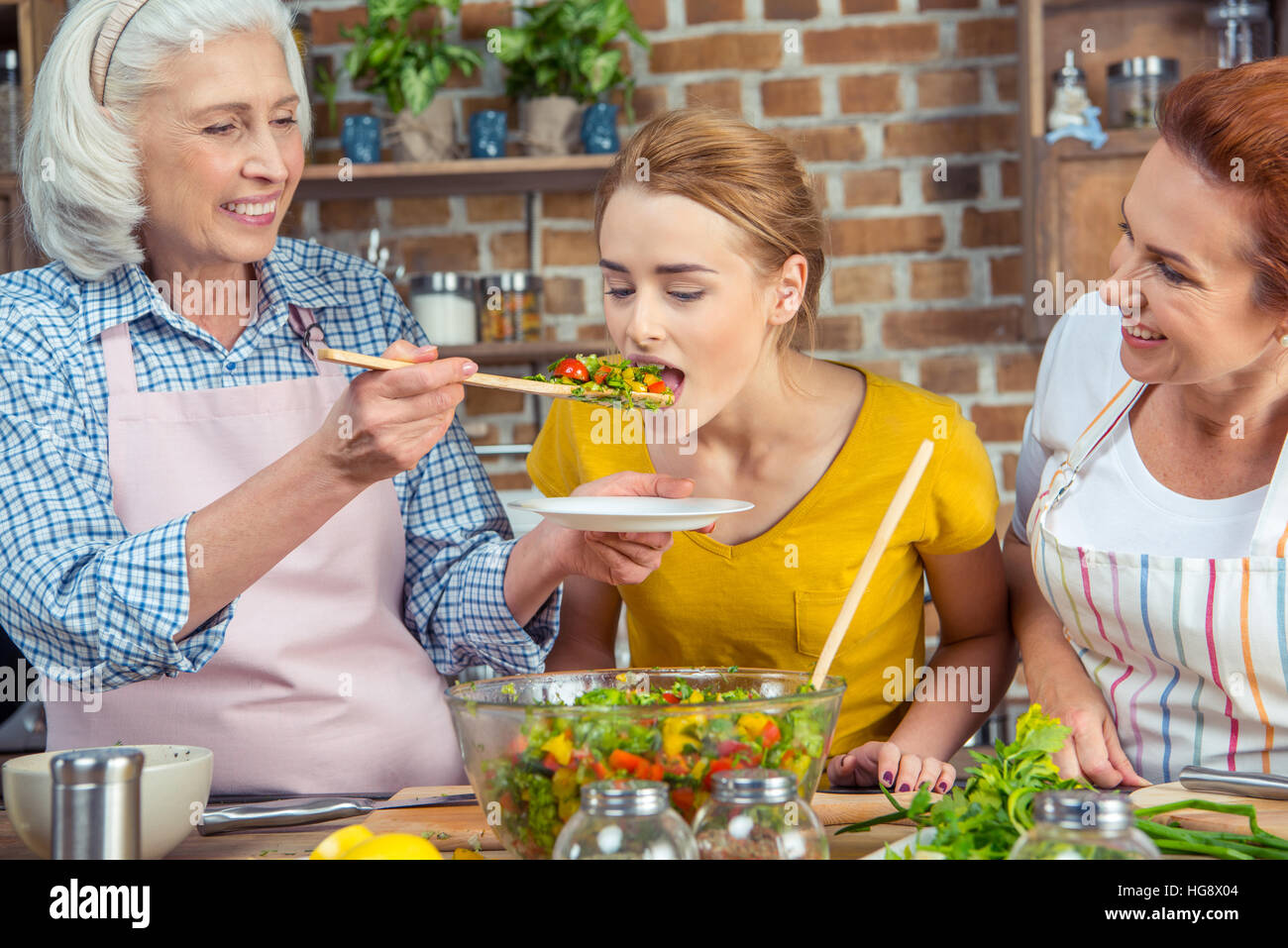 Young woman tasting fresh vegetable salad while standing with mother and grandmother in kitchen - Stock Image