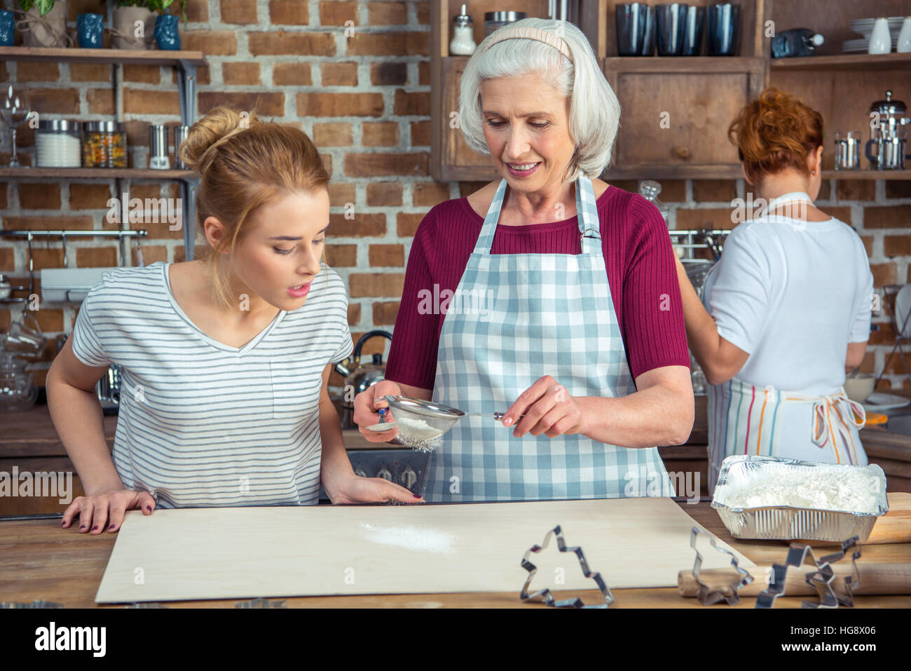 Grandmother and granddaughter sifting flour for cookies in kitchen - Stock Image