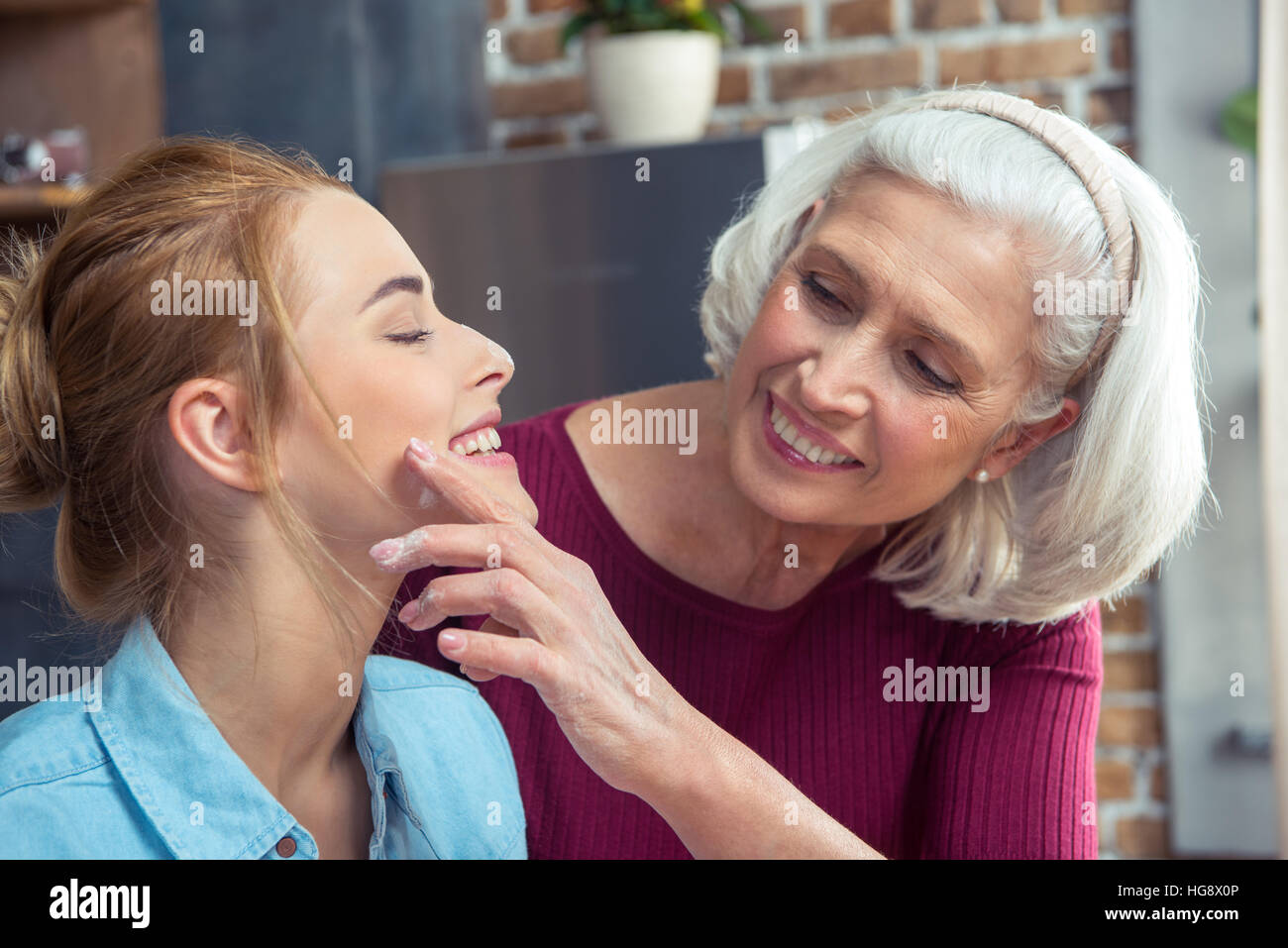 Happy grandmother removing flour from the cheek of her granddaughter - Stock Image