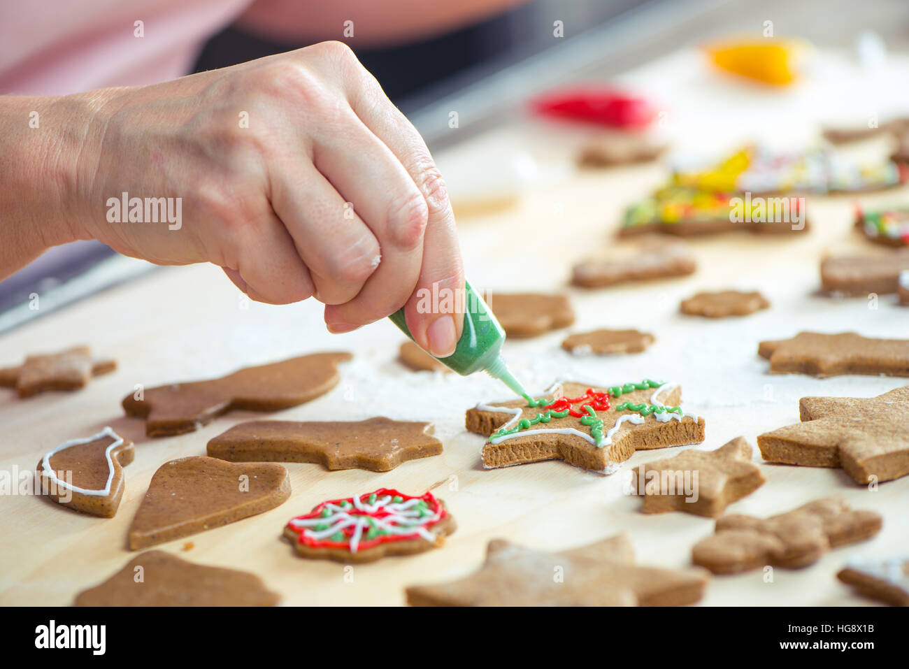 Partial view of woman icing Christmas cookies - Stock Image