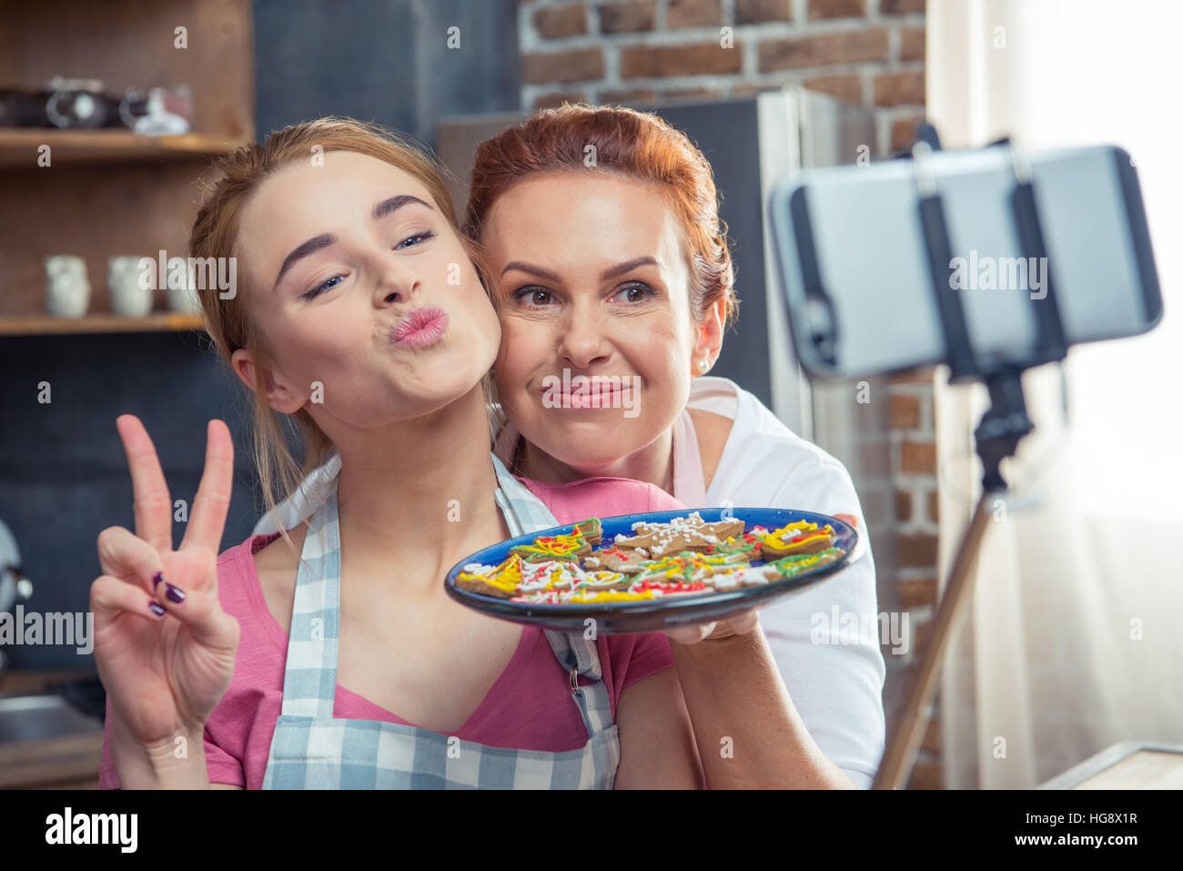 Mother and daughter making selfie holding plate with Christmas cookies - Stock Image