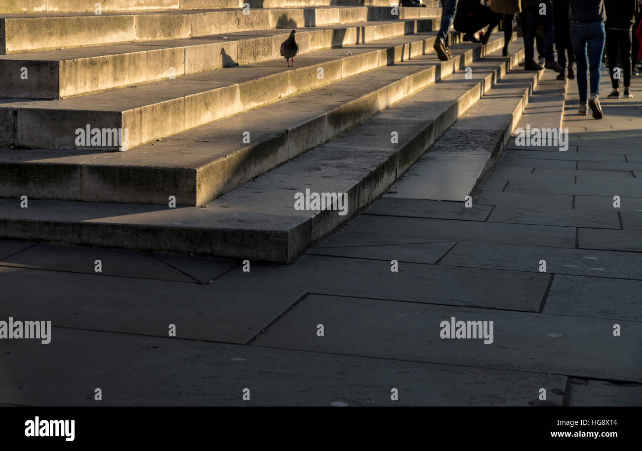 People (showing legs only) on the steps and pavement outside St Martin's in the Fields Church in Trafalgar Square. - Stock Image
