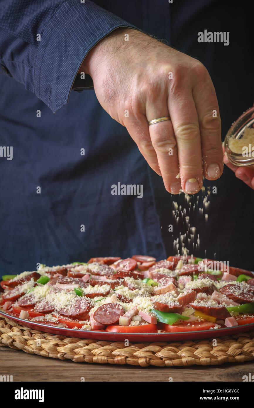 Man in a blue shirt sprinkle with cheese pizza on the table vertical - Stock Image