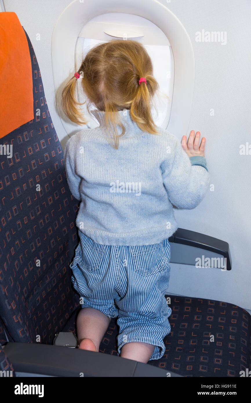 Child / toddler children age 2 on holiday vacation looking looks look out window flying on air plane / airplane Stock Photo