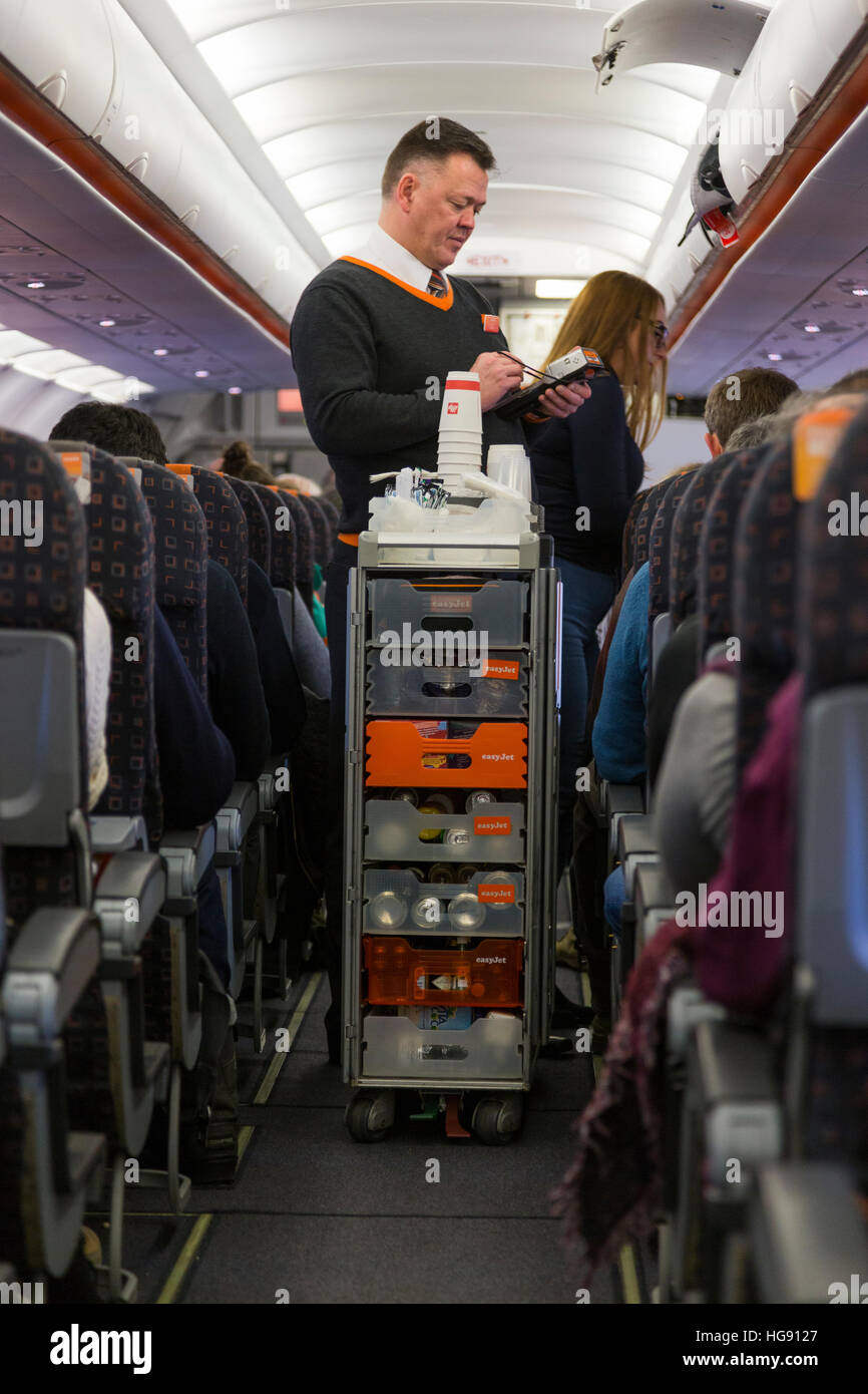 Cabin crew / air steward serves drinks and snacks to passengers – & takes payment – from a trolley cart during - Stock Image