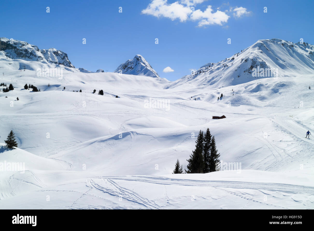 Ski pistes crossing alpine valley and rugged mountains, Paradiski, Plagne, Alps, France - Stock Image