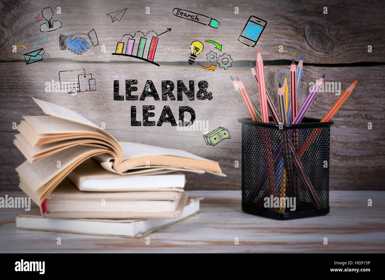 Learn and Lead. Stack of books and pencils on the wooden table. - Stock Image