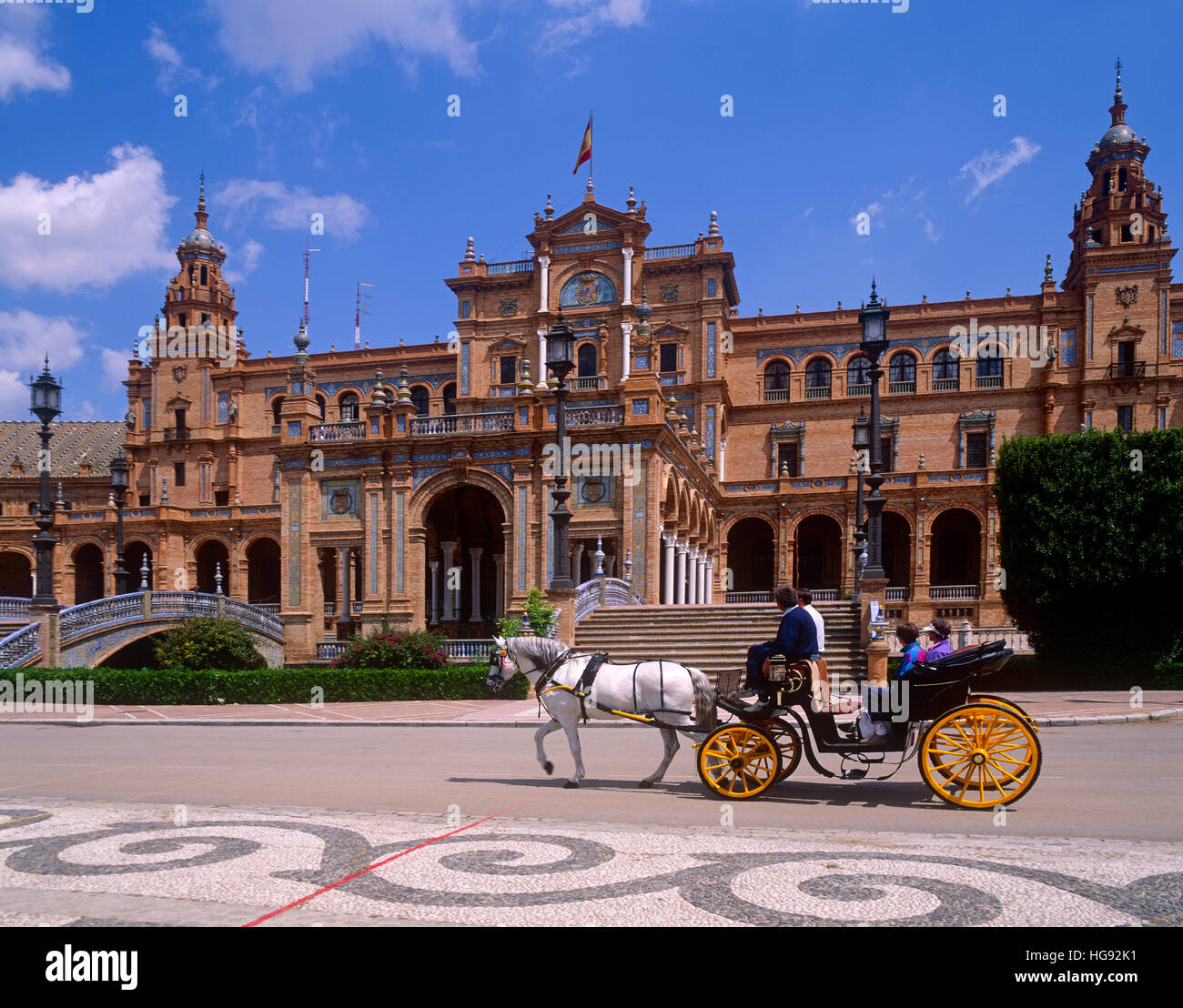 Tourists in Horse drawn carriage at the Plaza de Espana, Seville, Andalucia, Spain - Stock Image