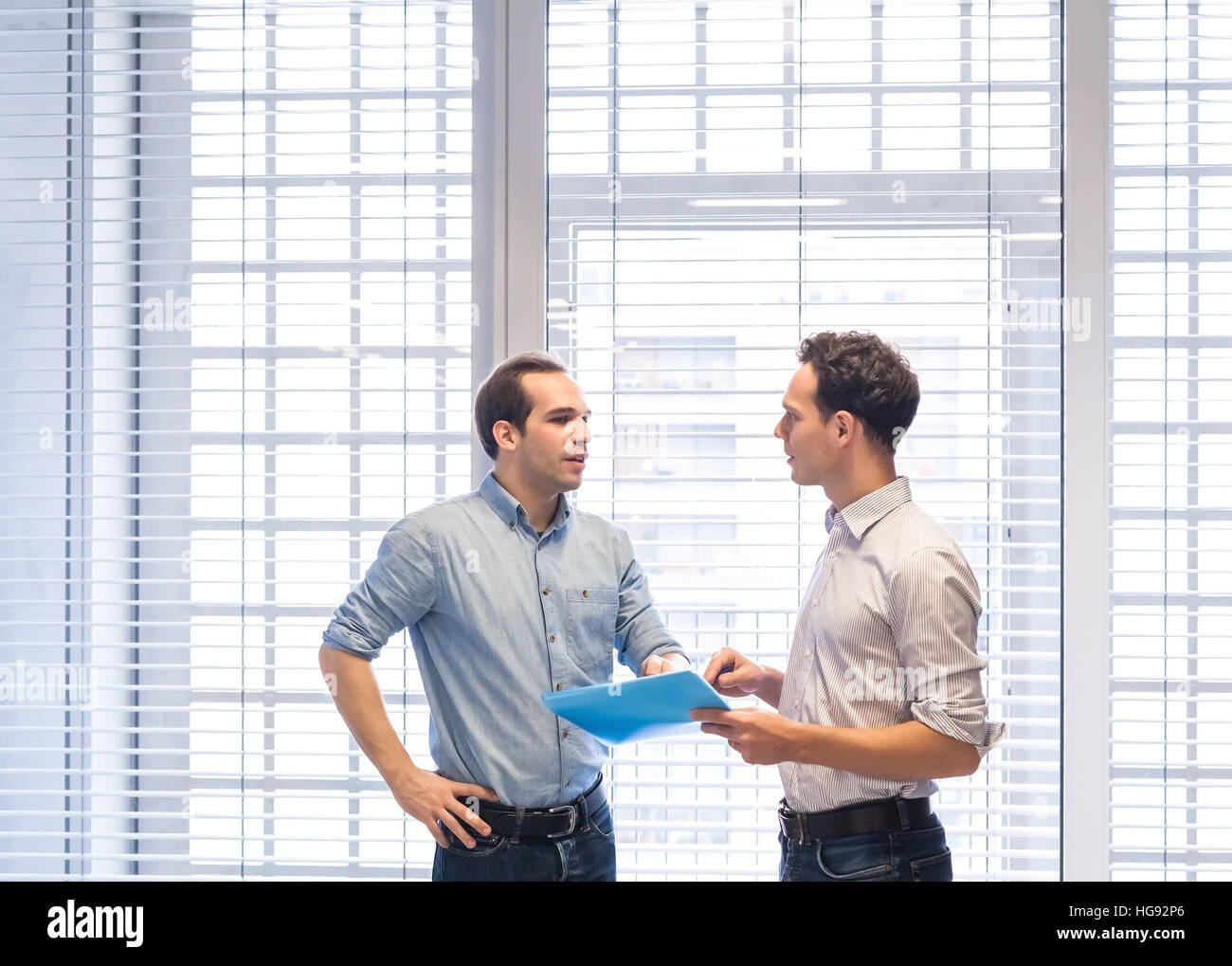 Two colleagues speaking together about project documents standing in bright modern office interior - Stock Image