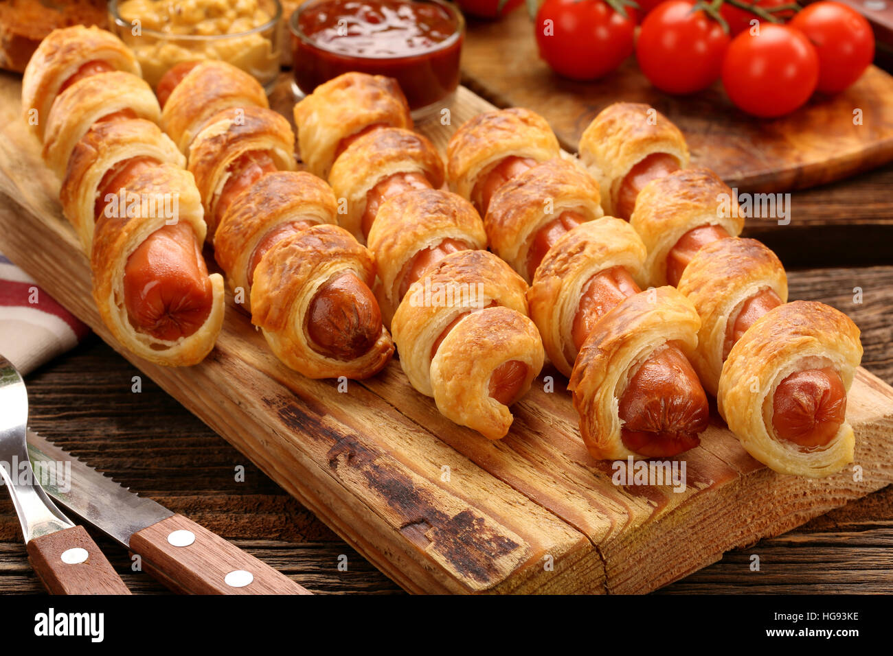 Rolled hot dog sausages baked in puff pastry on wooden background - Stock Image