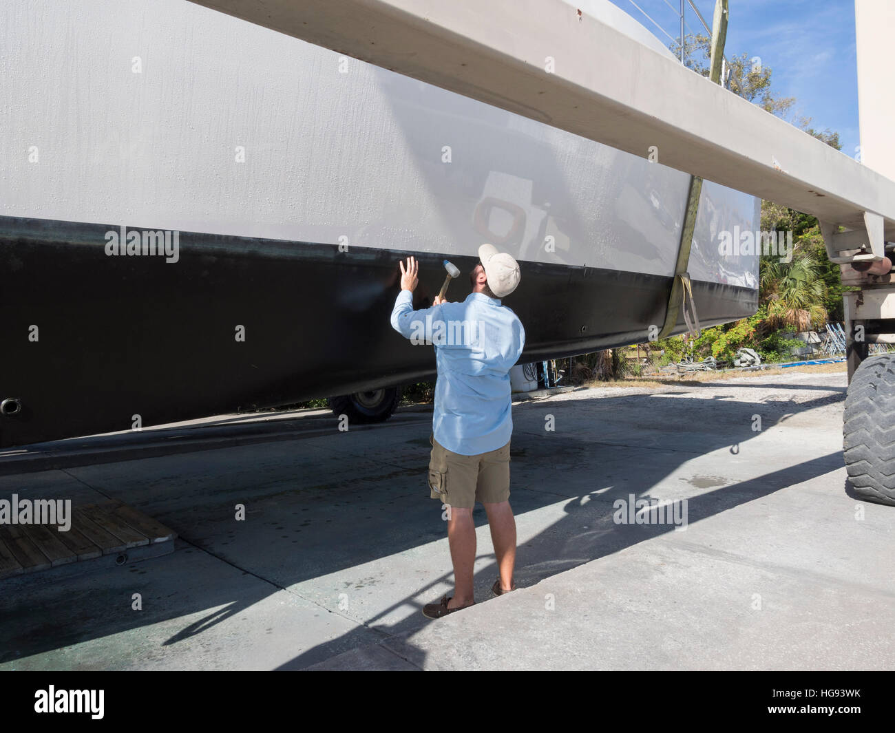 A surveyor checks the condition of the hull on a hauled out boat - Stock Image