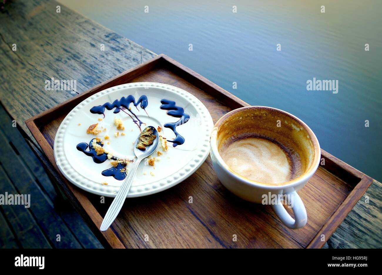 Empty coffee cup and white plate with crumbles of eaten cake and used spoon  dirty after finish breakfast. & Empty coffee cup and white plate with crumbles of eaten cake and ...