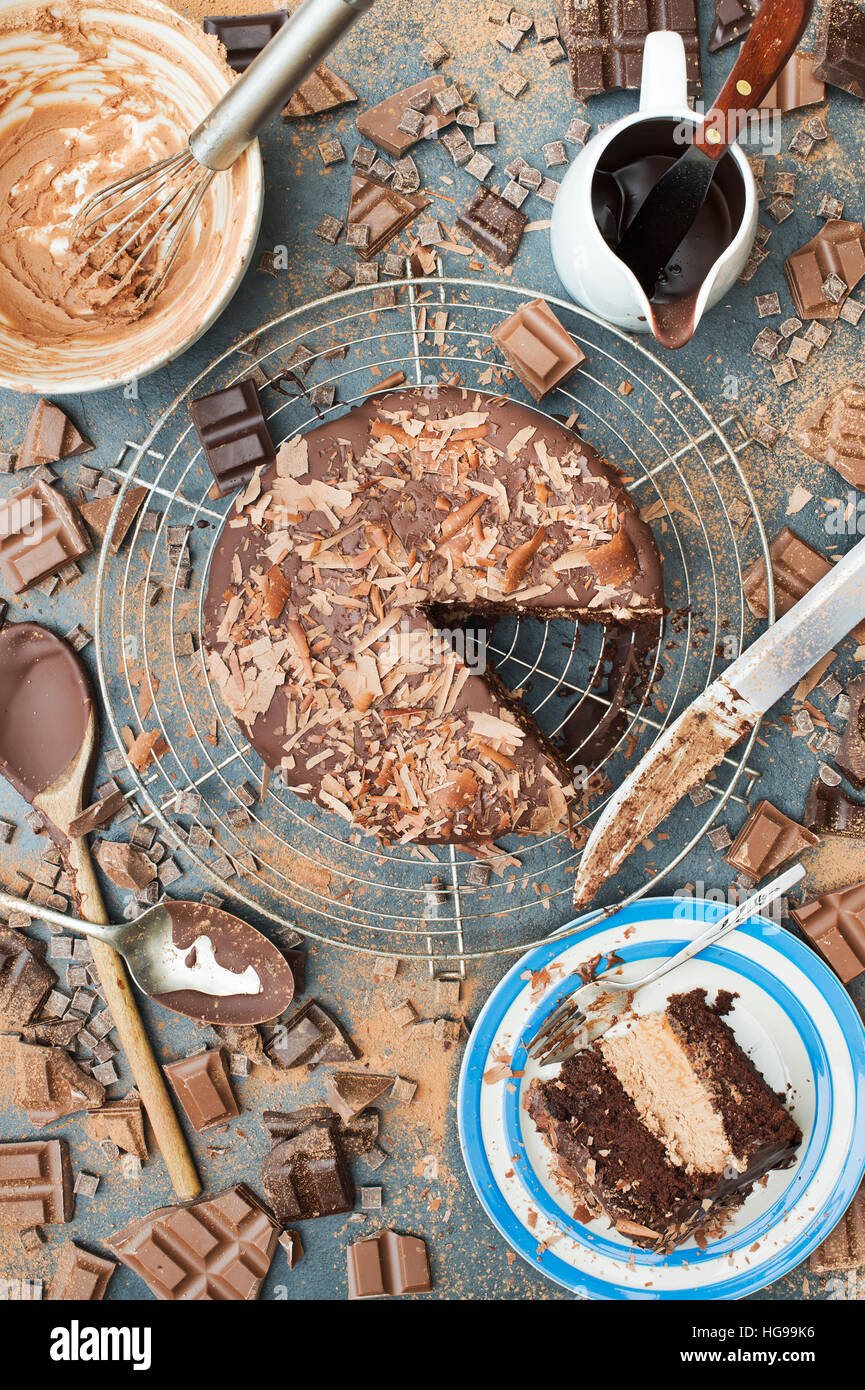 A mess of chocolate. Chocolate cake, bars, chunks and powder pattern on slate - Stock Image