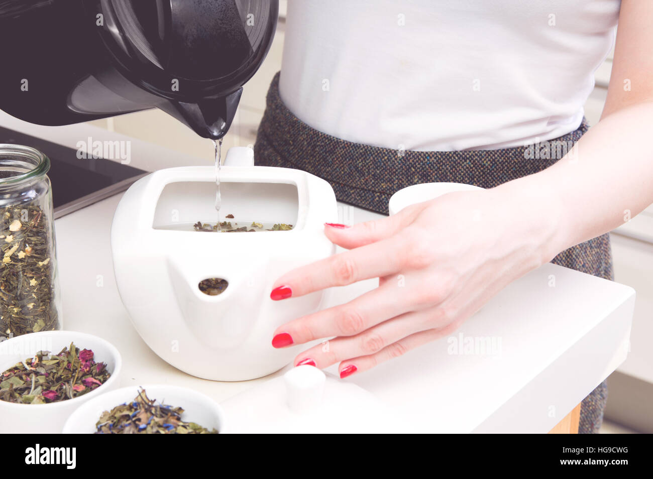 Woman poured hot water into the kettle with green tea. Photography ...