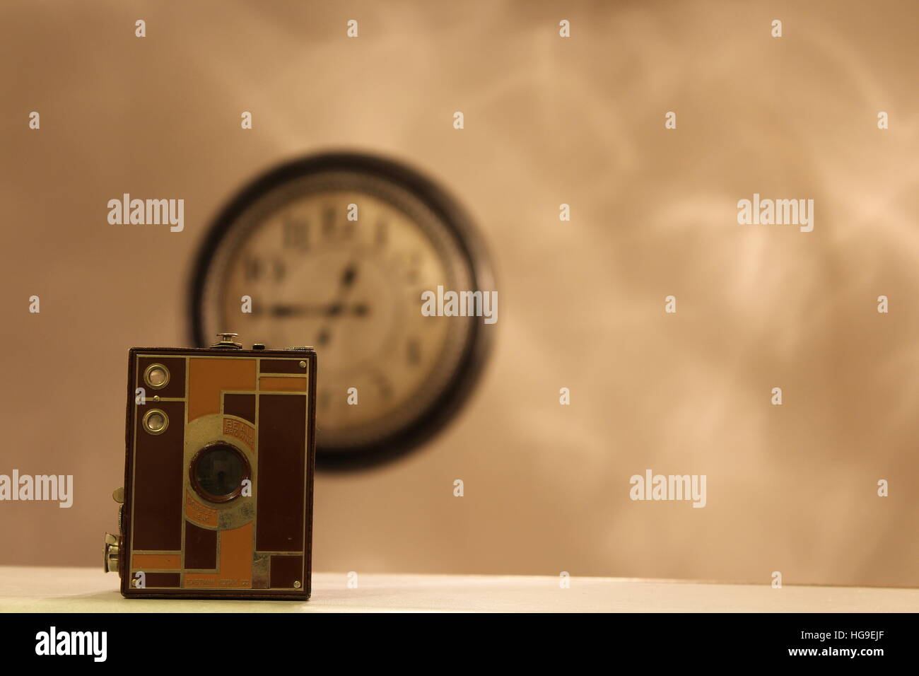 Old brownie camera with an oversize wall clock - Stock Image