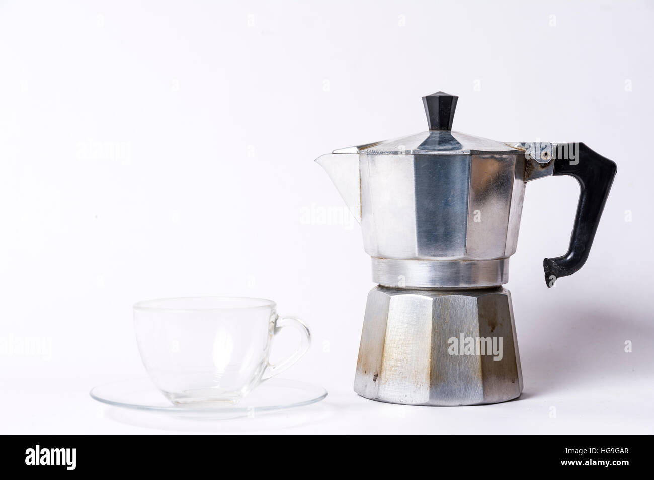 Italian coffee maker and an empty coffee cup on a white background - Stock Image