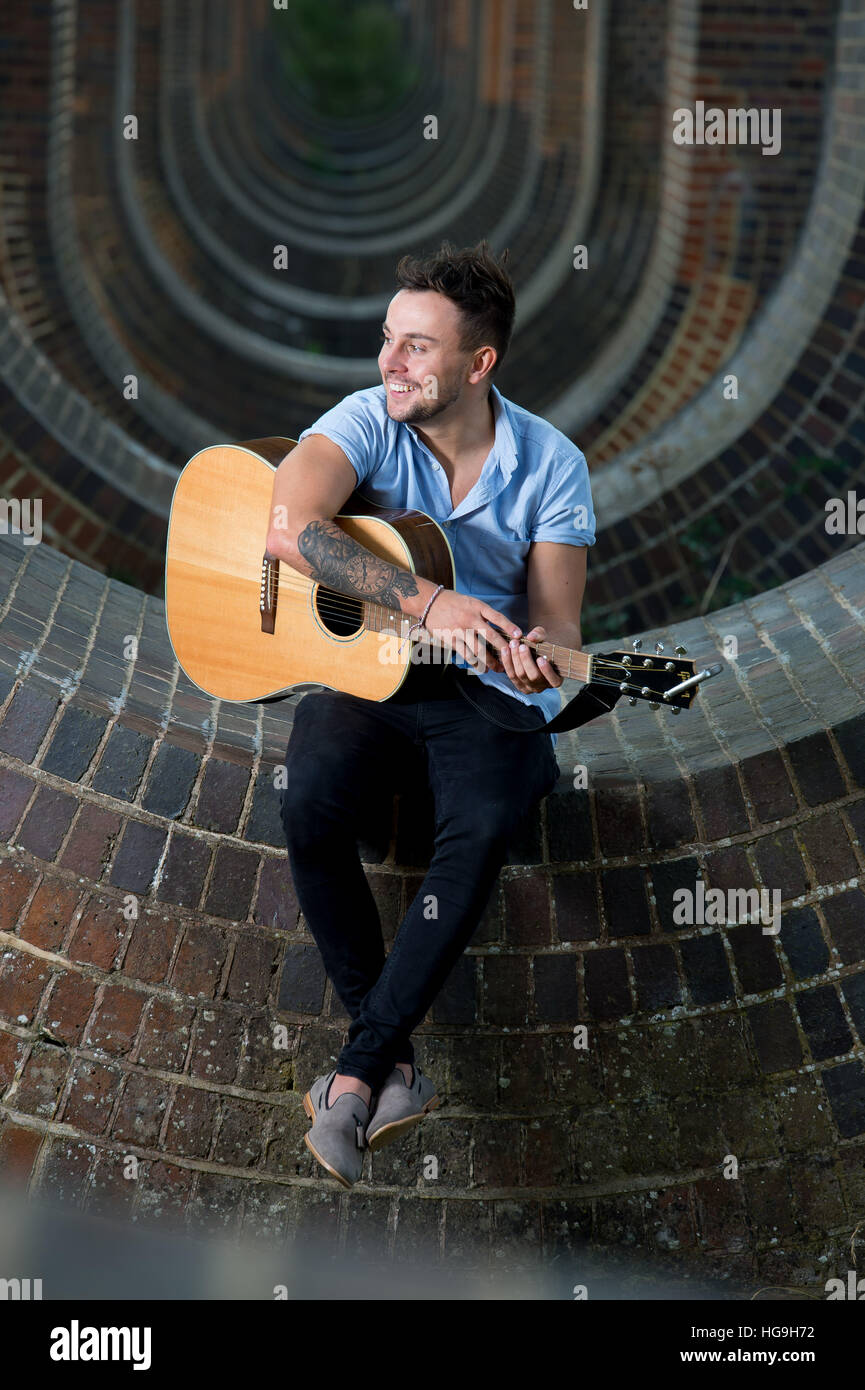 Singer, songwriter Jamie Mathias poses with his guitar for a shoot at the Ouse valley viaduct, Sussex, UK. - Stock Image