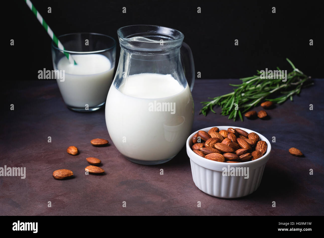 Homemade almond milk on dark rusty background over black background. Dairy free vegan milk. Toned image - Stock Image