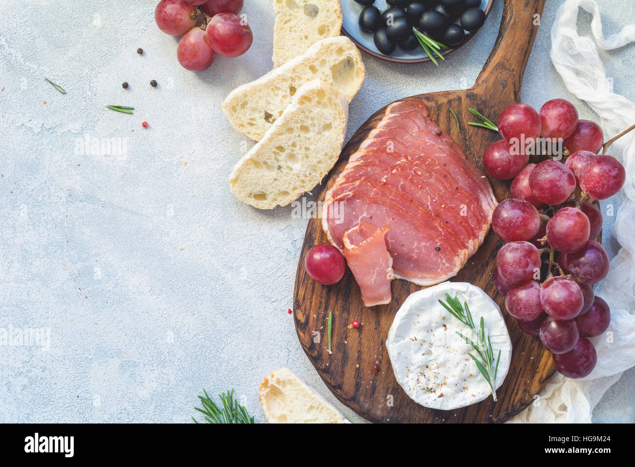 Appetizer plate with fresh baguette, cured meat, grapes, cheese and olives. Antipasti or tapas concept. Top view, - Stock Image