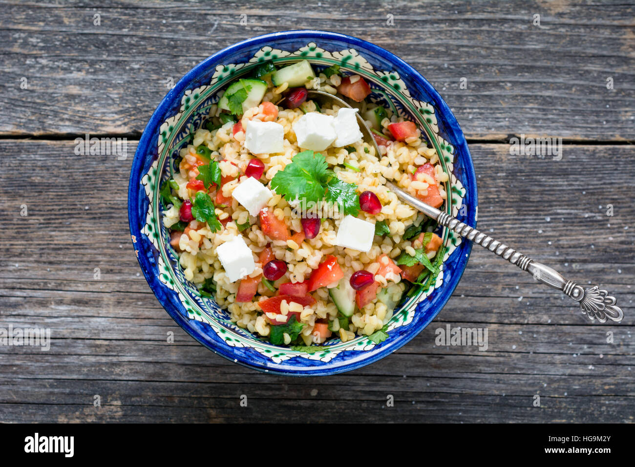 Tabbouleh salad with soft white cheese and pomegranate seeds in bowl on wooden background - Stock Image