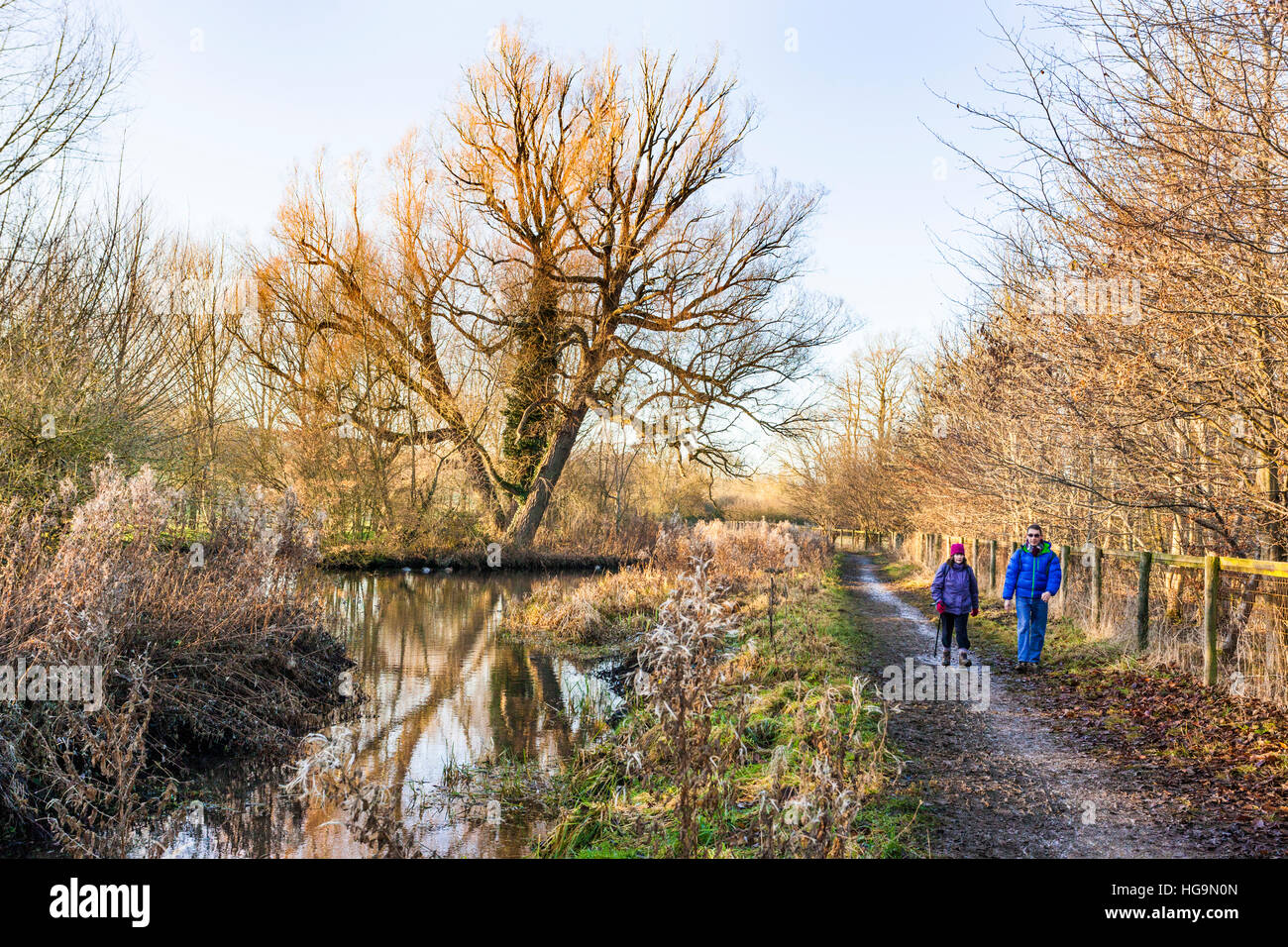 A couple enjoying a winter walk beside the River Eye near the Cotswold village of Lower Slaughter, Gloucestershire - Stock Image