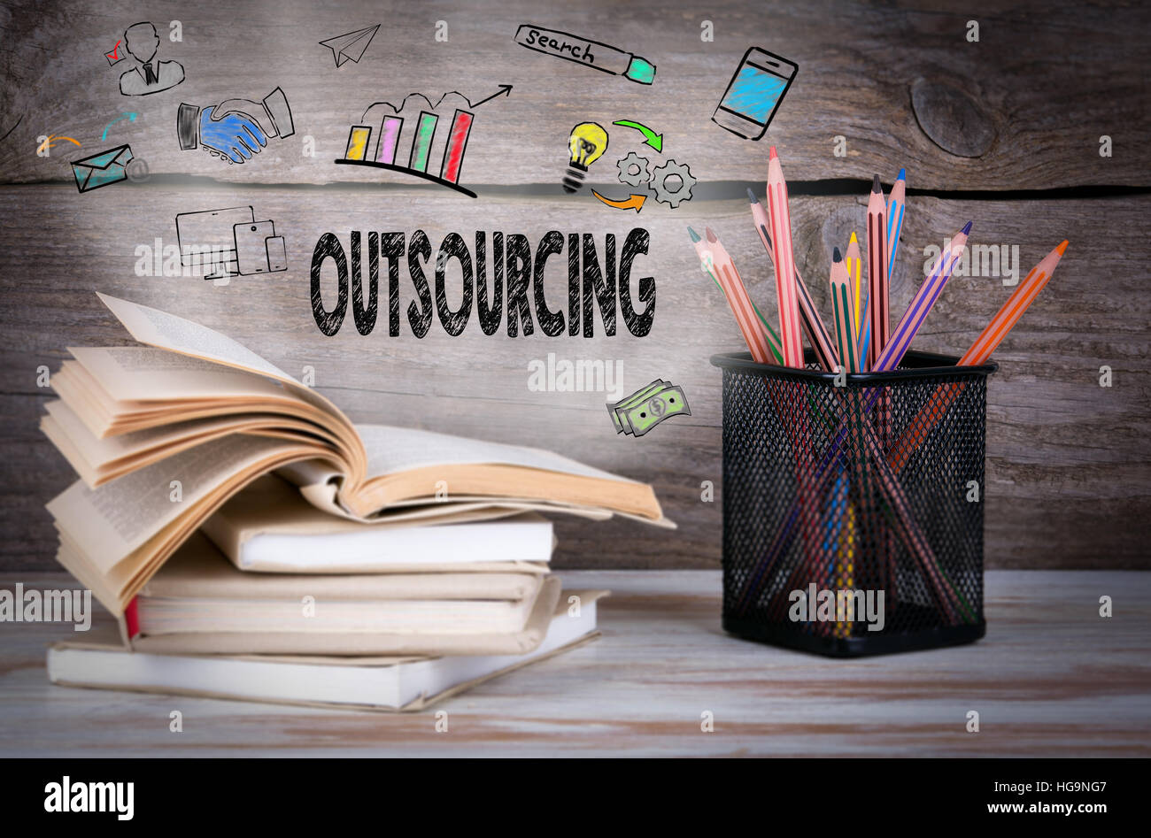Outsourcing, Business Concept. Stack of books and pencils on the wooden table - Stock Image