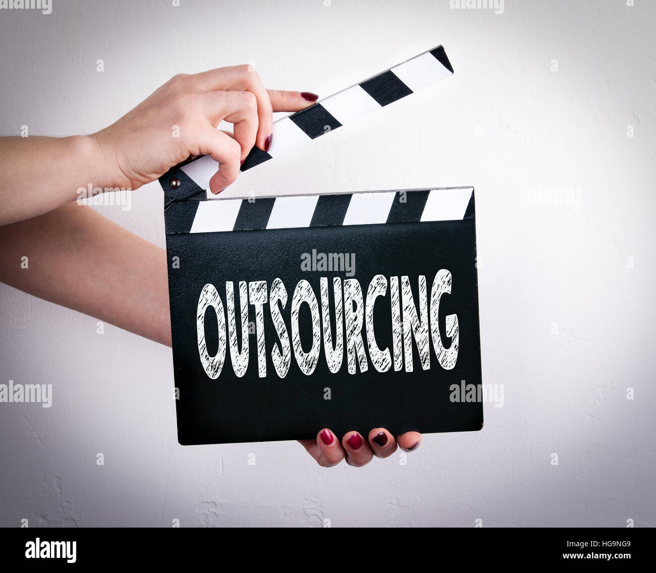 Outsourcing. Female hands holding movie clapper - Stock Image