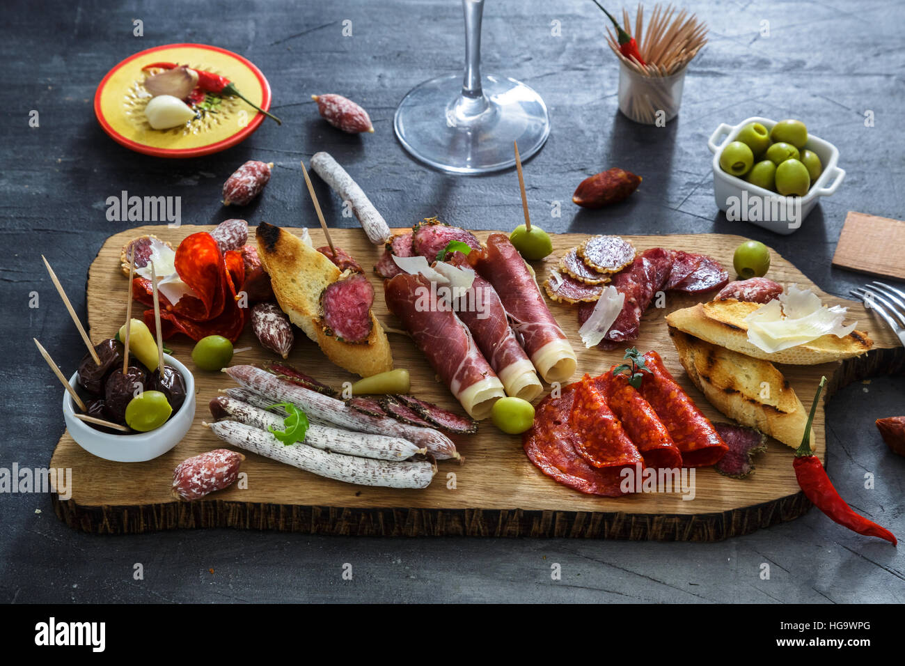 Mix of different snacks and appetizers. Spanish tapas on a black stone background.  bar. Space for text. Deli, sandwiches, - Stock Image