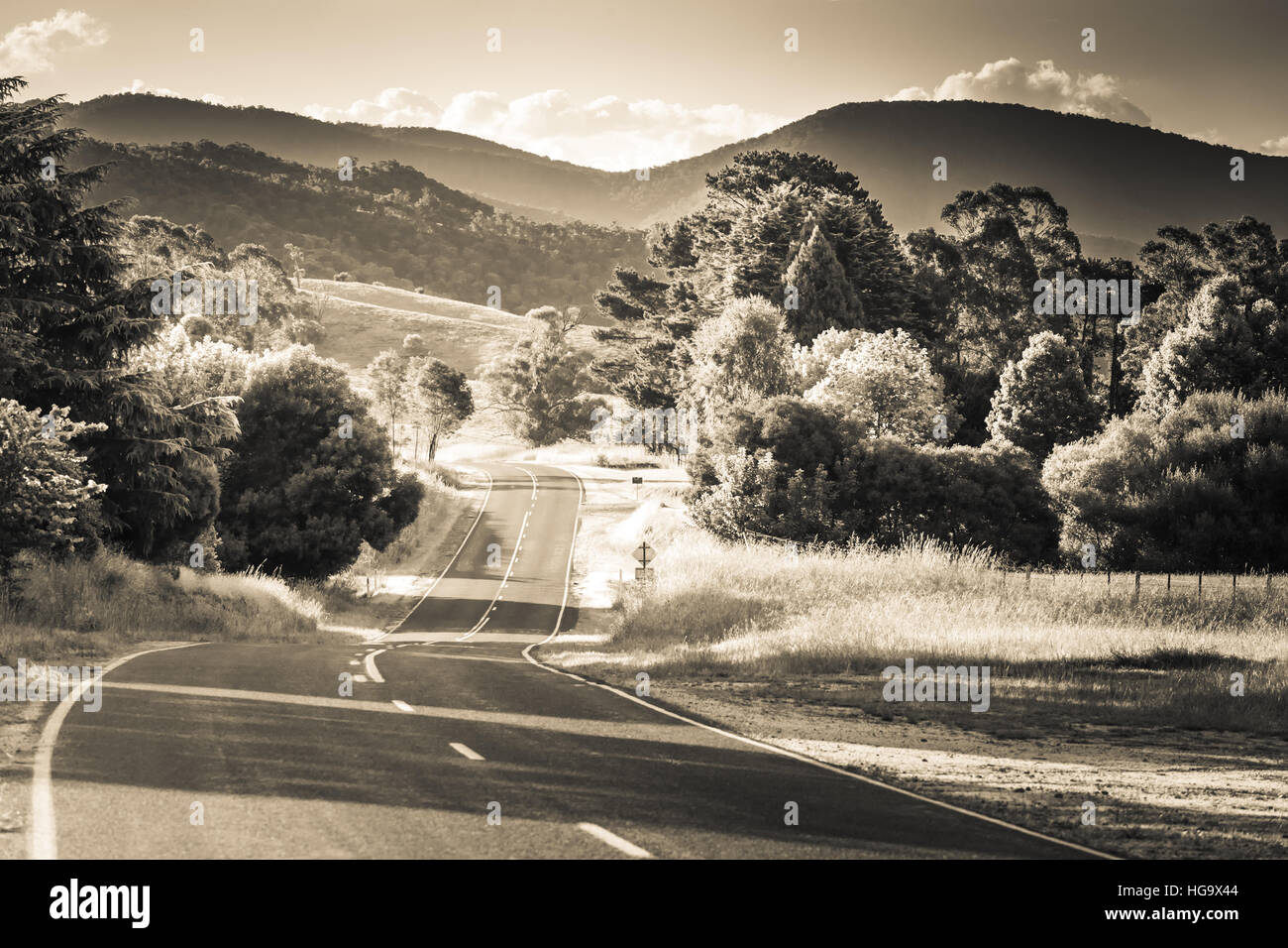 Black and white landscape. Rural road in Australian countryside at sunset - Stock Image