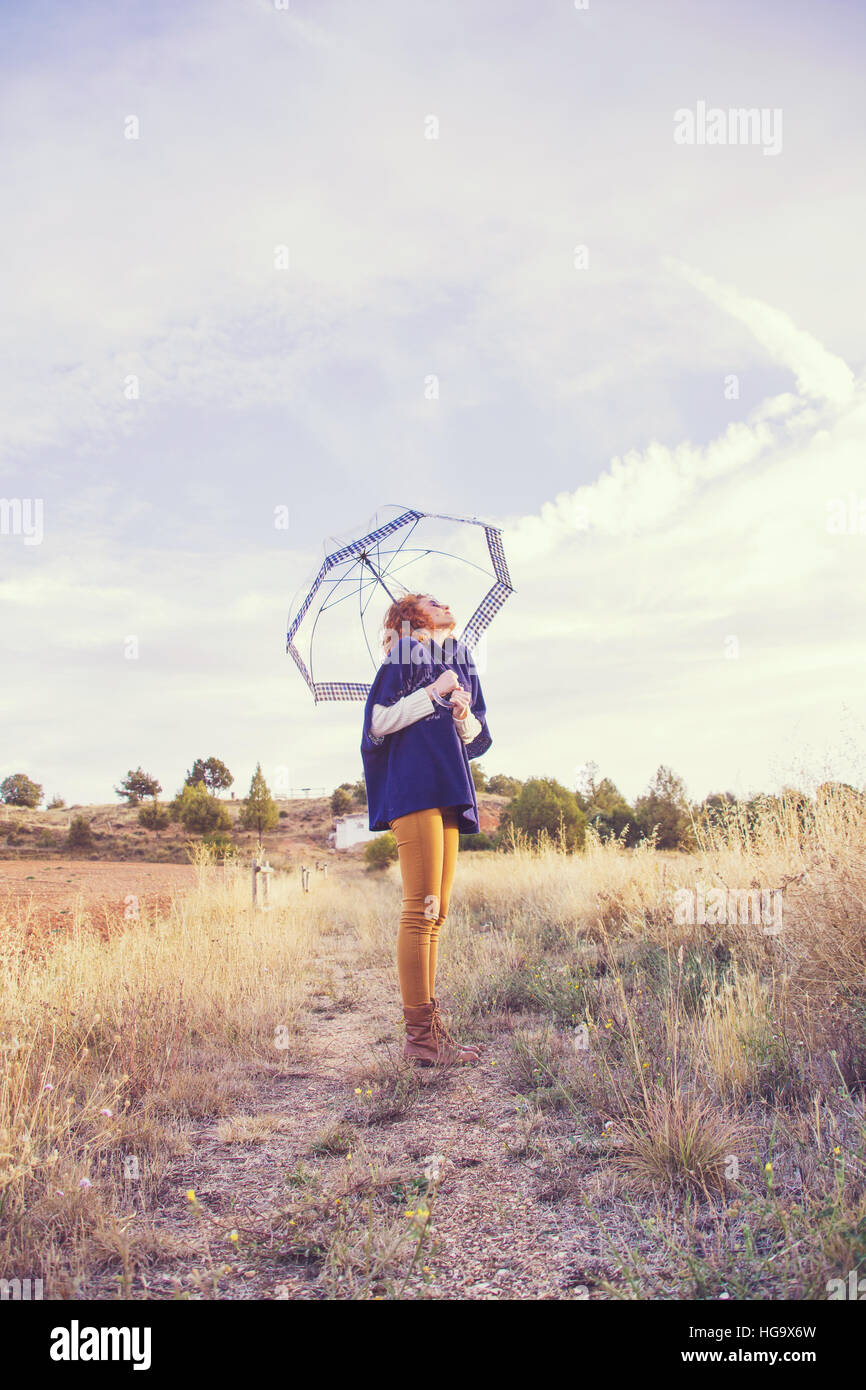Woman with a transparent umbrella y a sunny autumn day - Stock Image