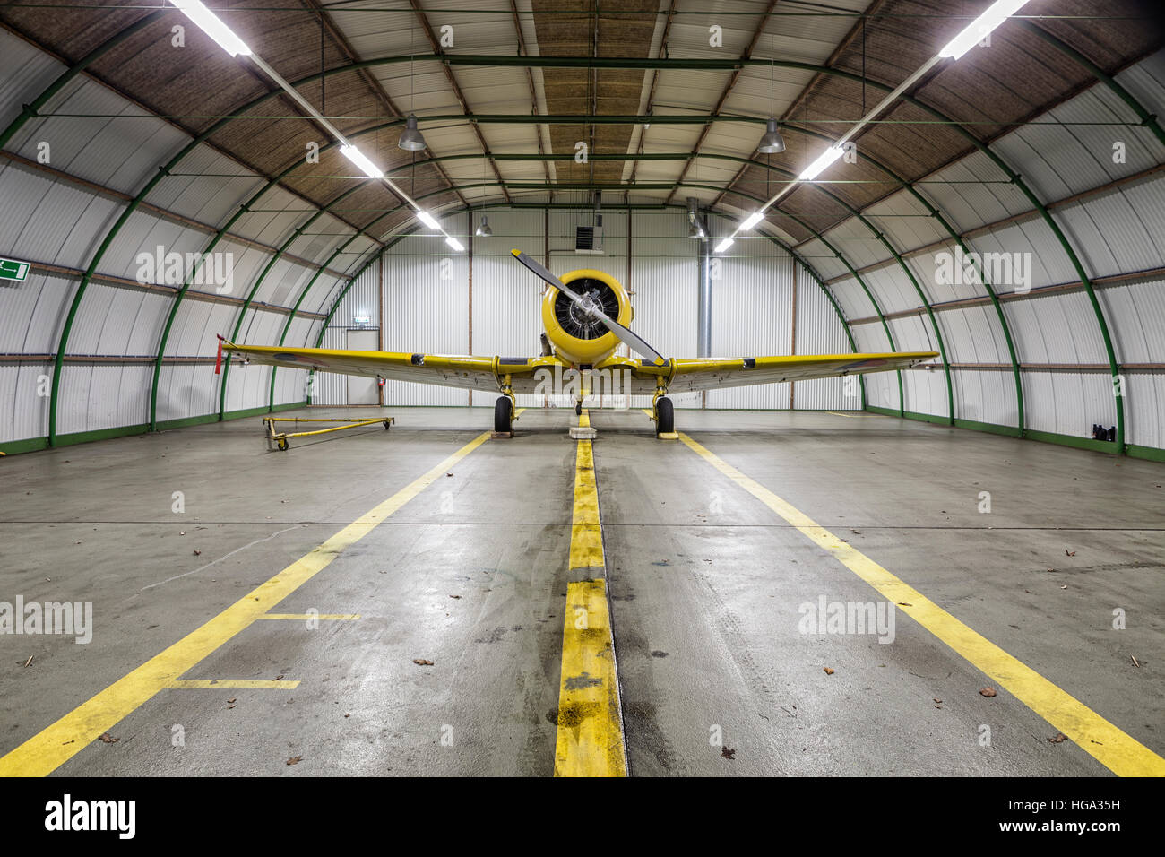 Vintage old yellow war plane inside of a clean empty hangar - Stock Image