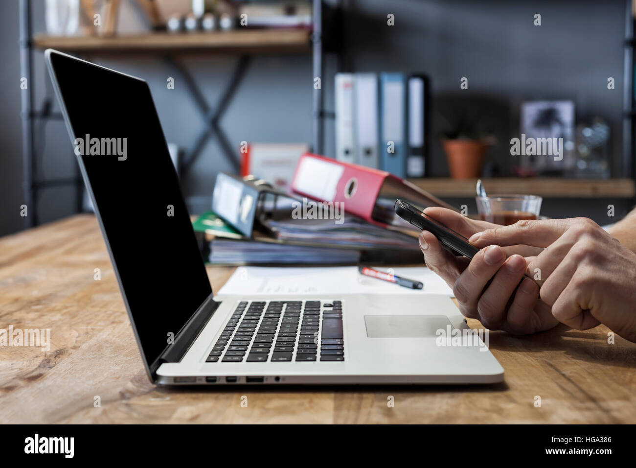 Man working at his home with laptop, moblie phone and documents at the dinner table Stock Photo