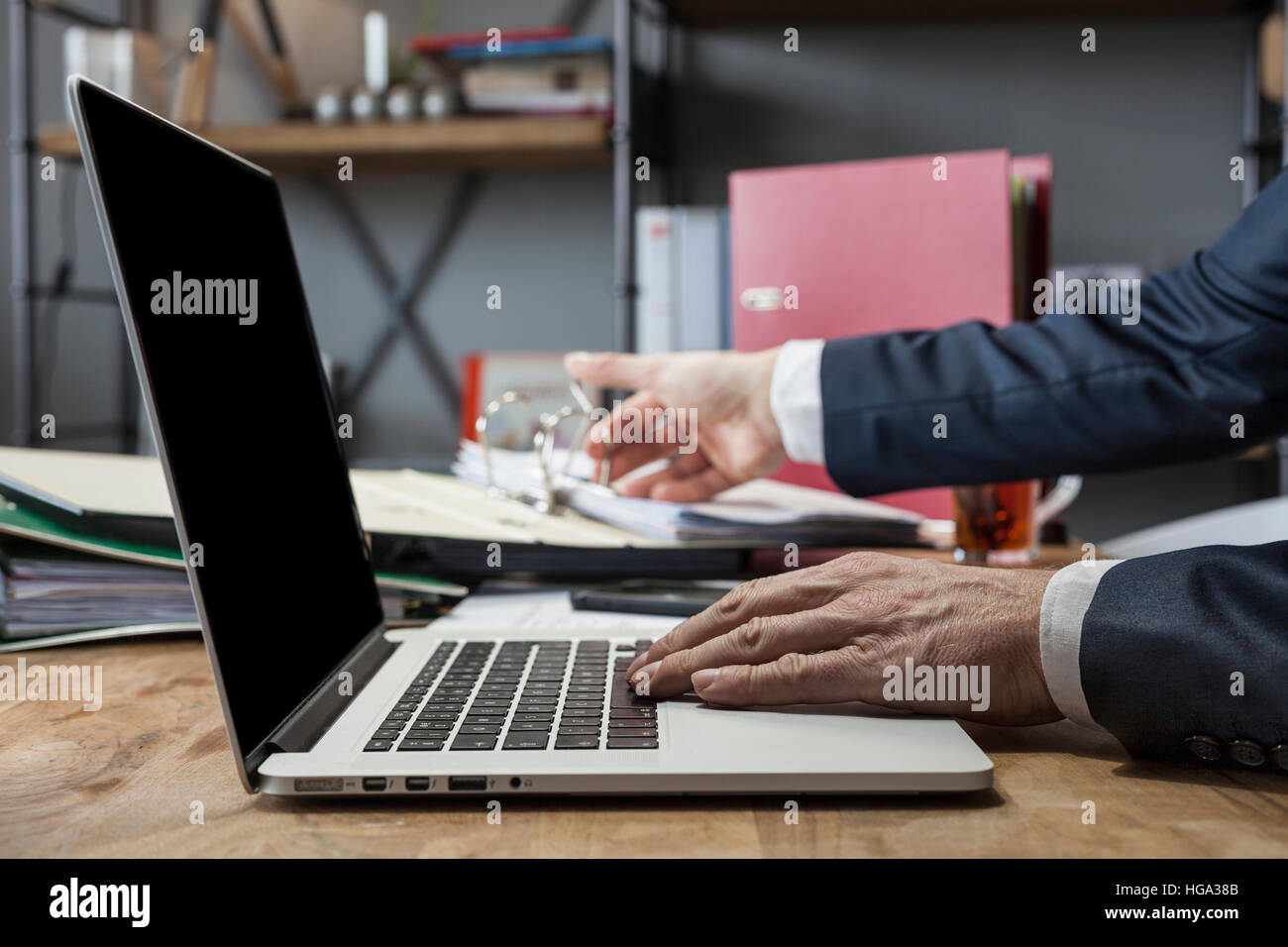 Unrecognizable man using a modern portable computer on an wooden table at home - Stock Image
