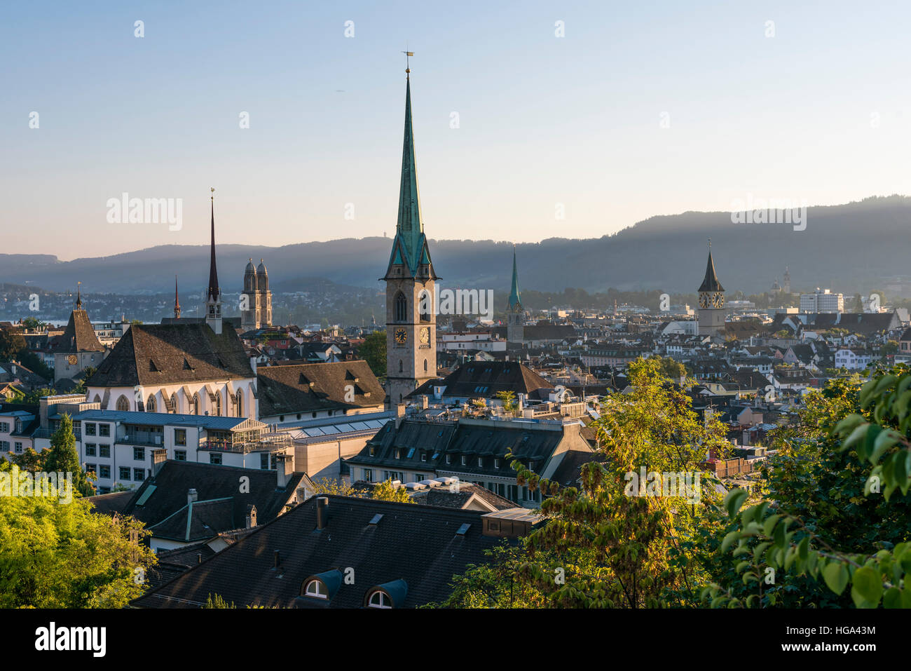 Zurich city panorama with Grossmunster cathedral, Predigerkirche, Fraumunster and St. Peter in the setting sun. - Stock Image