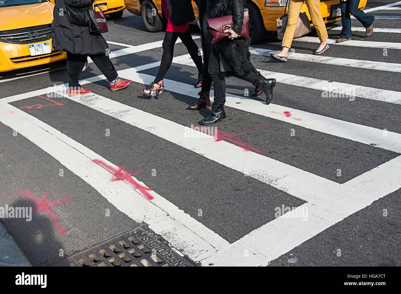 People crossing a crosswalk in New York city. - Stock Image