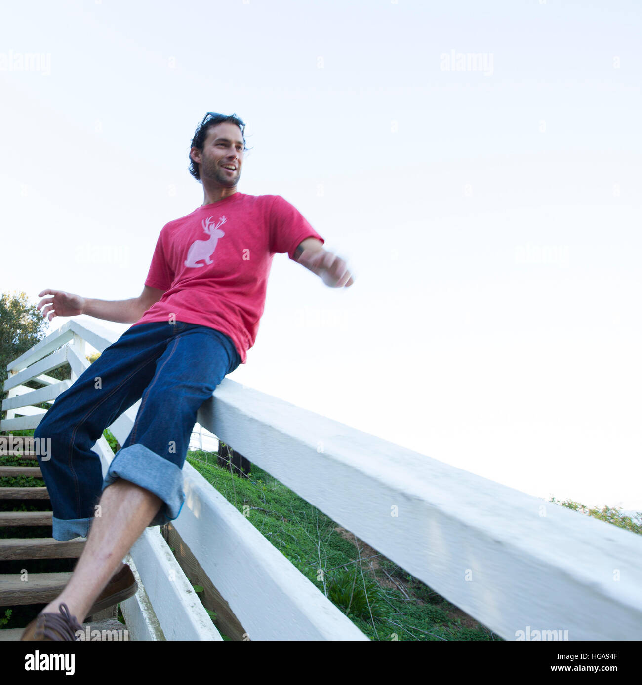 A Young Man Sliding Down A Stairway Railing Stock Photo