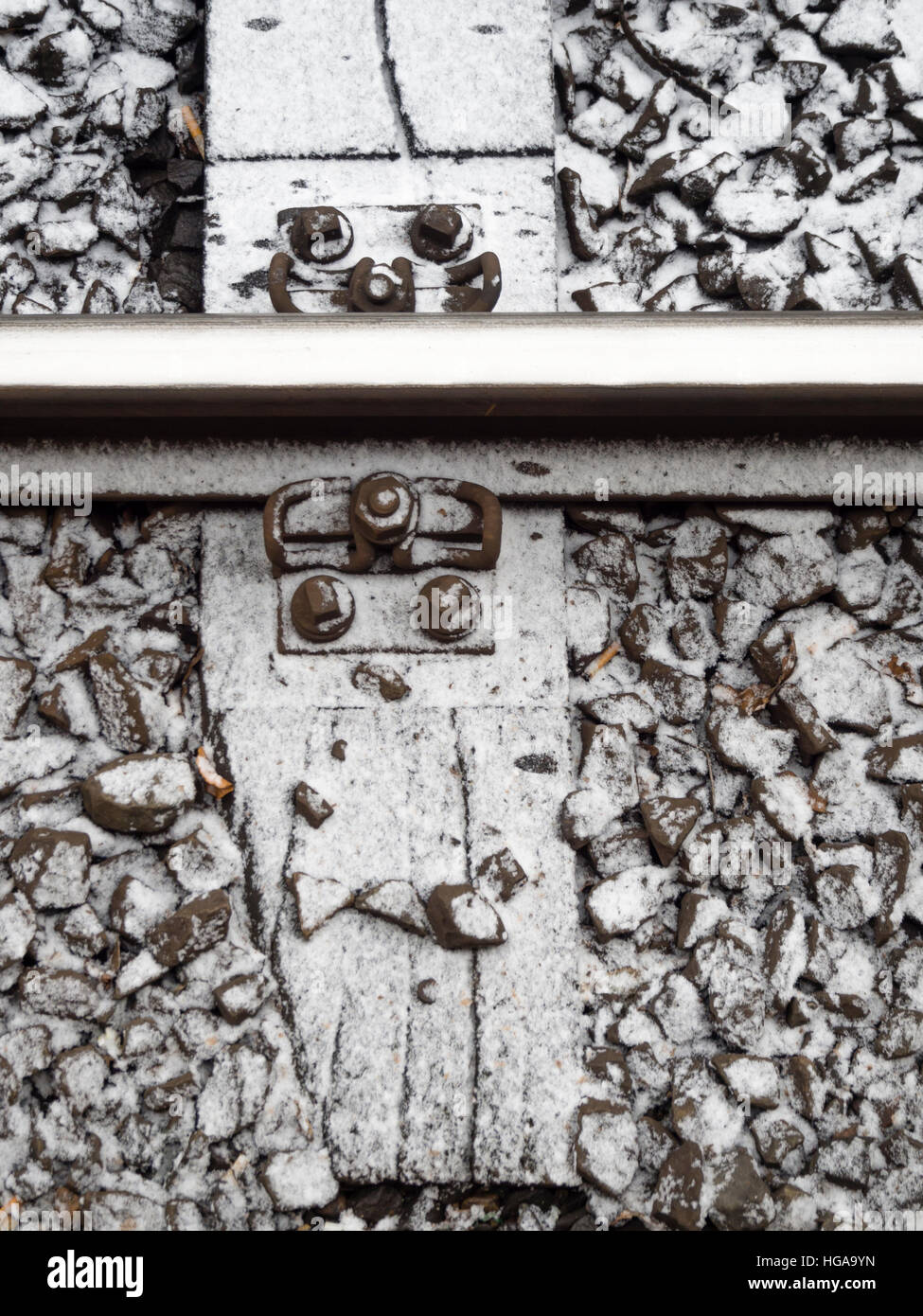 Close-up view from above onto snow covered railway tracks - Stock Image